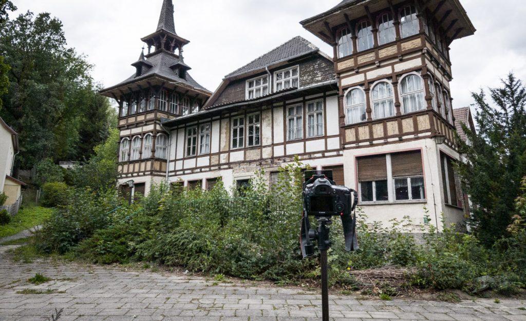 Die Kamera auf dem Stativ macht eine Aufnahme vom Reichsbahnerholungsheim in Alexisbad