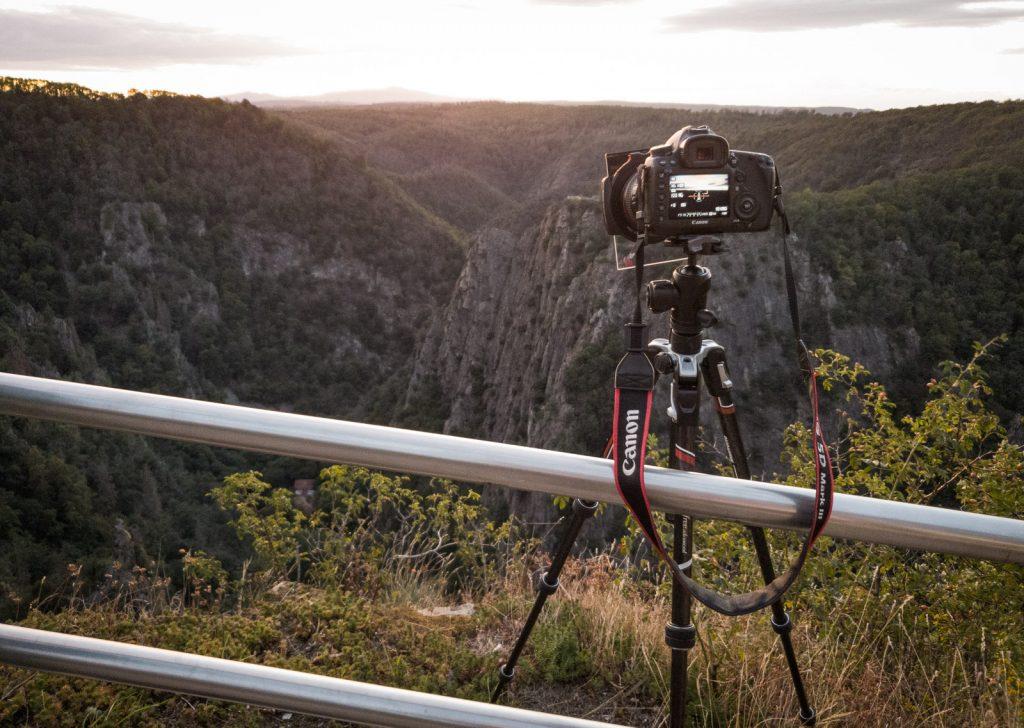 Eine Kamera auf einem Stativ fotografiert das Bodetal vom Hexentanzplatz aus