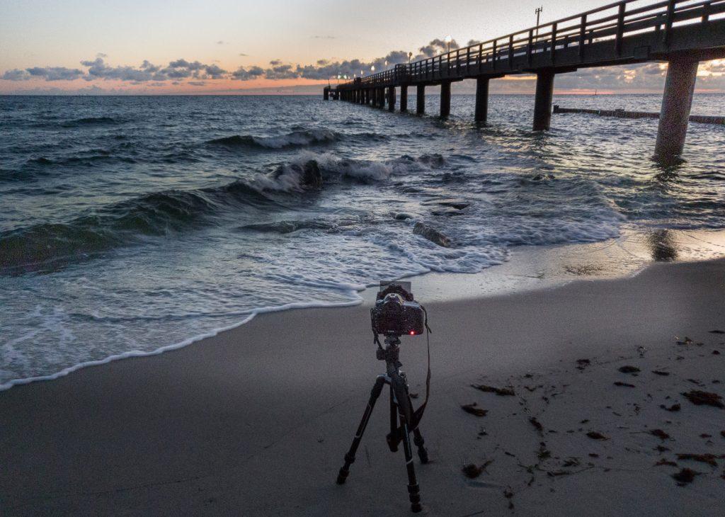 Eine Kamera auf dem Stativ fotografiert den Sonnenaufgang an der Seebrücke Kühlungsborn