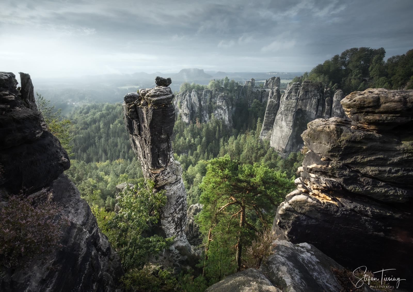 Die Wehlnadel in der Sächsischen Schweiz im Sonnenaufgang an einem nebligen Tag