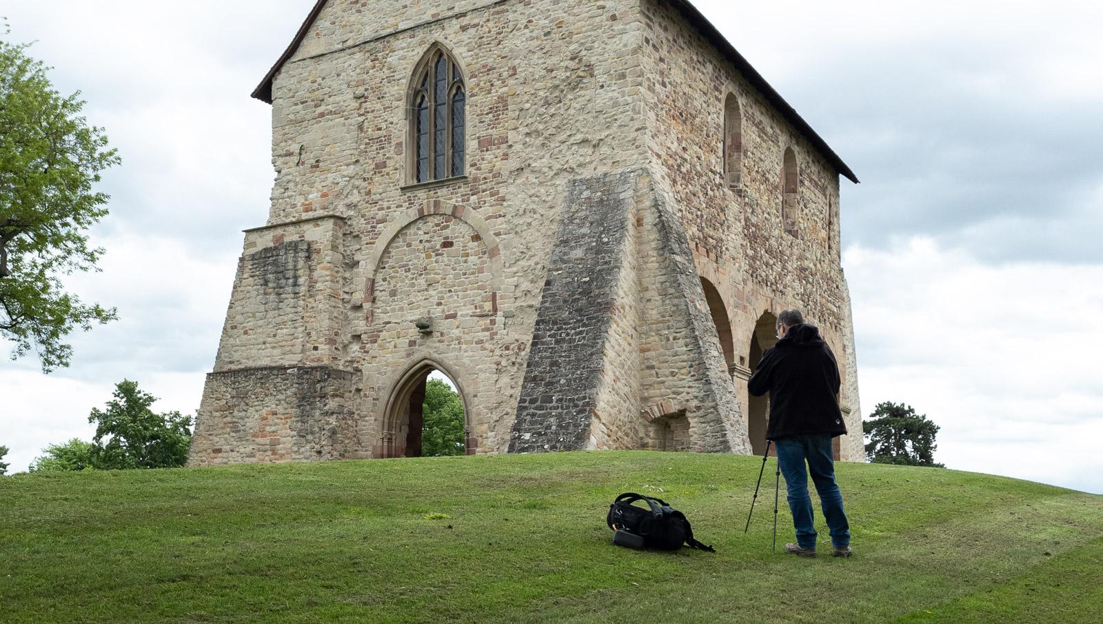 Fotograf steht mit einer Kamera auf einem Stativ vor dem Kloster Lorsch