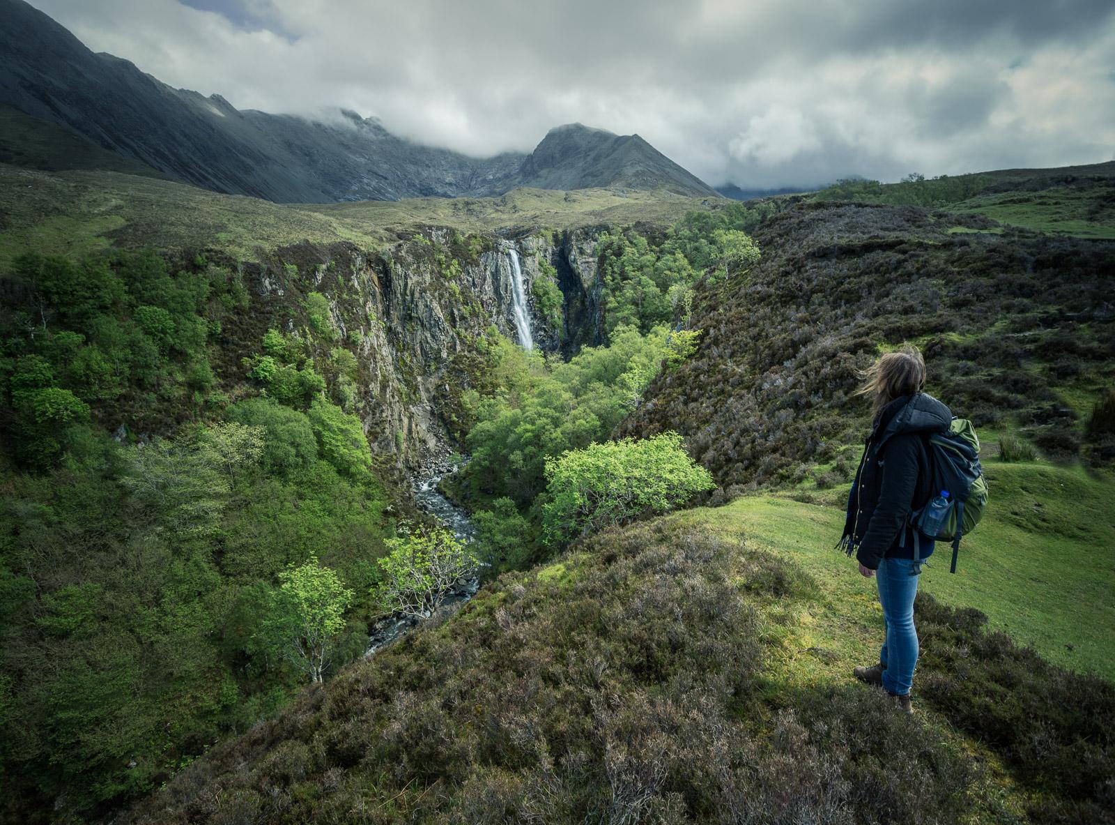 Frau schaut zum Eas Mor Waterfall (Wasserfall).